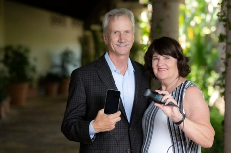 Sally Palmer, with her husband Greg, showing the handheld Butterfly iQ ultrasound device