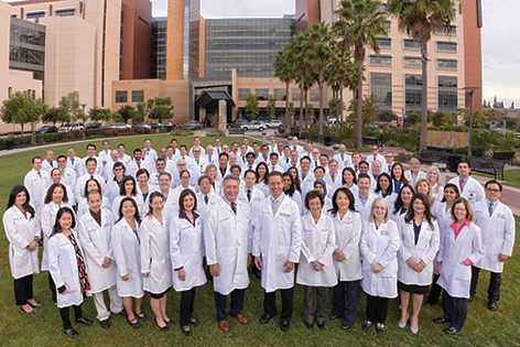 UC Irvine Health faculty members named Physicians of Excellence gather in front of Douglas Hospital. In the center foreground are Dr. Manual Porto, left, and Dr. Michael J. Stamos, dean of the medical school.Dr. Manual